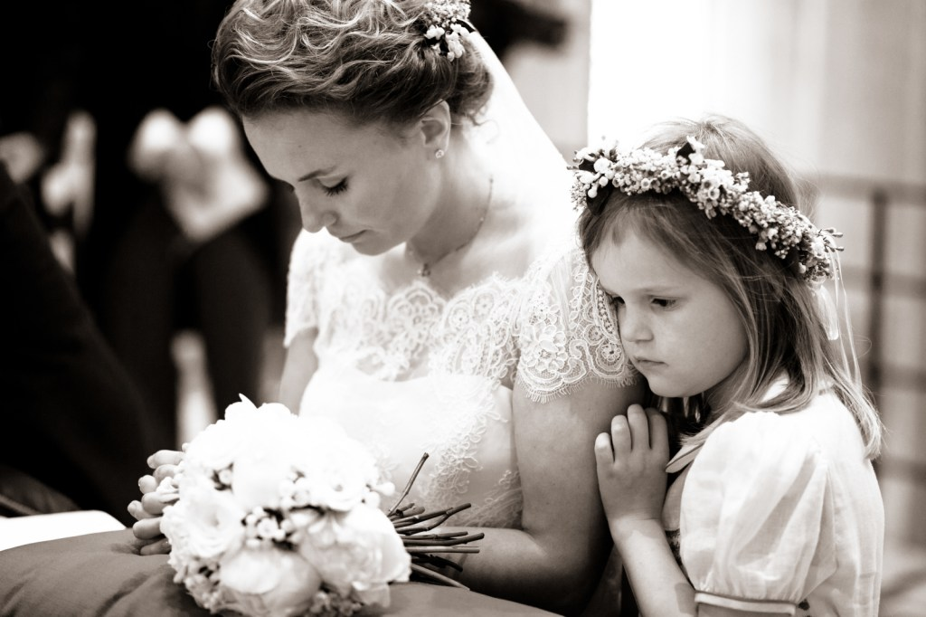 flower girl next to praying bride, wedding in Veneto, Italy